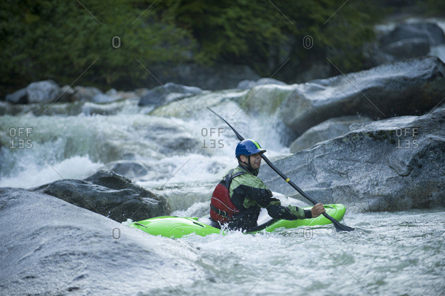 A whitewater kayaker sits in an eddy after running a series of rocky drops.