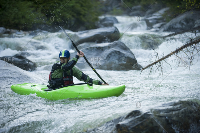 A whitewater kayaker continues down a rocky section of a high mountain river.