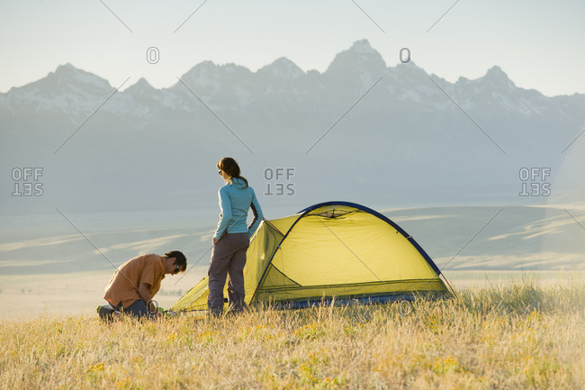 A young couple set up their tent on a summer evening.