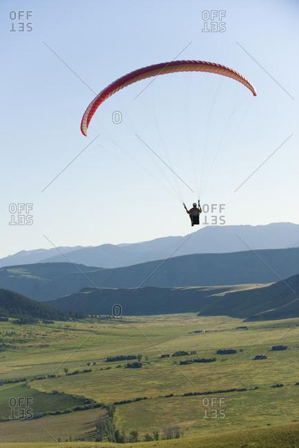 A paraglider flies high above a valley.