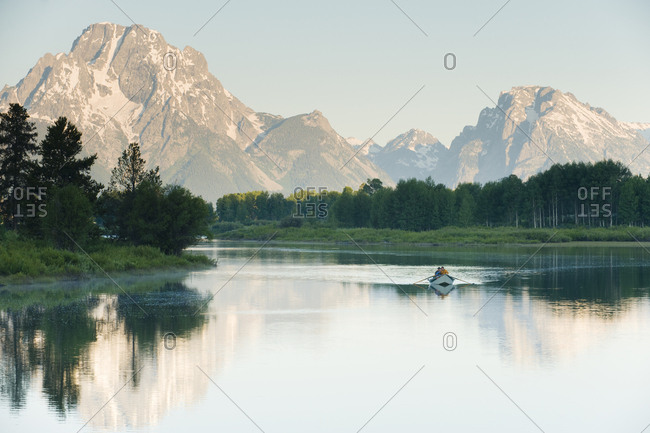 A lone drift boat floats in the reflected waters of a river.