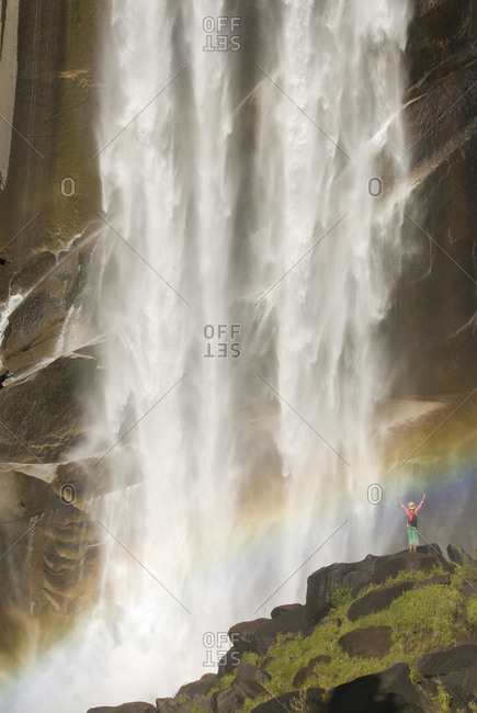A young woman celebrates under a giant waterfall.