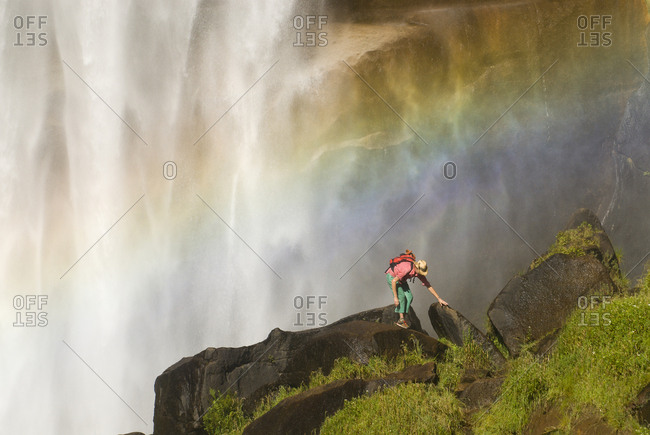 A young woman explores beneath a giant waterfall.