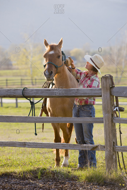 A woman grooms her horse before an evening ride.