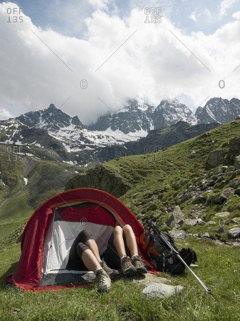 Hikers' legs protrude from tent in alpine meadow, mountains