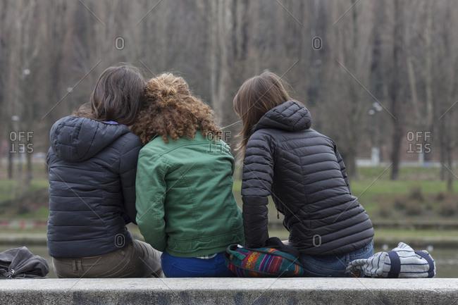 Teen girls relax on bench, sharing music