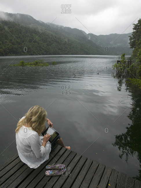 Mature woman works on tablet on dock in mountain lake