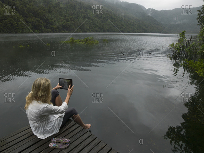 Woman takes photo with tablet on dock in mountain lake