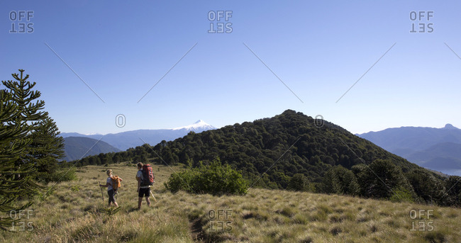 Couple of hikers on alpine ridge with volcano behind