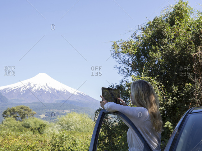 Woman takes photo of volcano with tablet from car