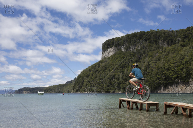 Bicyclist contemplates scene from small dock on mountain lake
