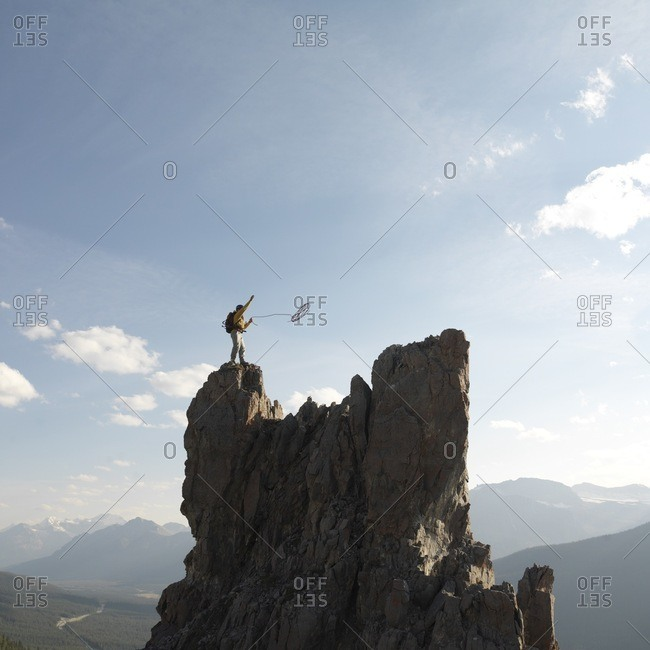 Mountaineer throws rope, mountain summit