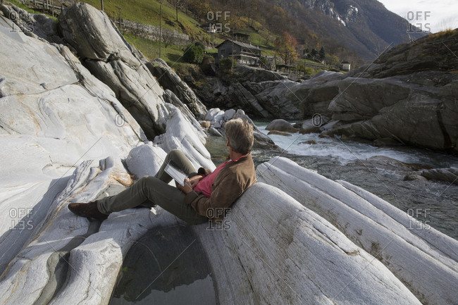 Man uses digital tablet  in river canyon
