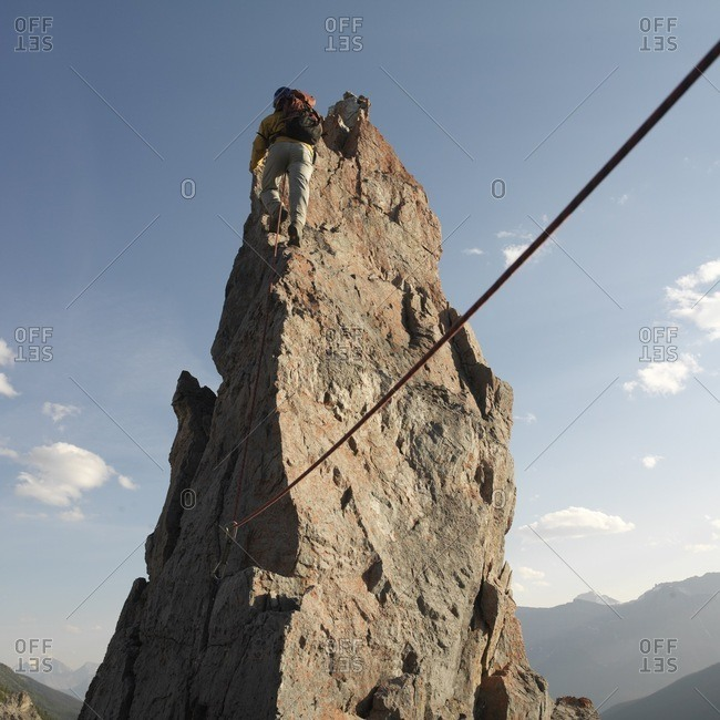Climber ascends pinnacle above mountain range