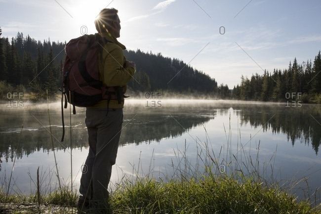 Hiker pauses at edge of mountain lake, sunrise