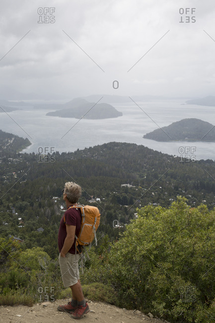 Mature hiker pauses on trail above lakes and mountains