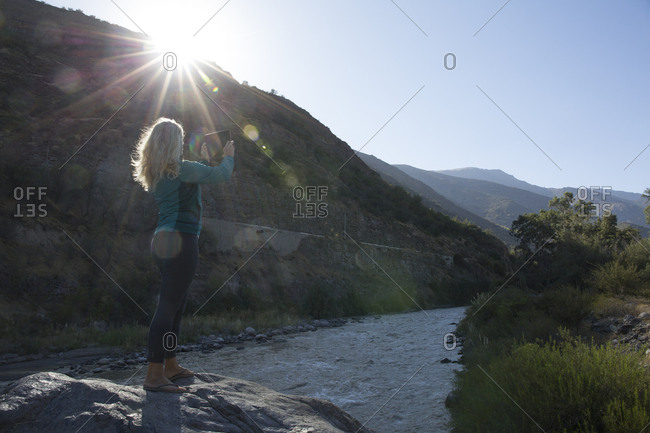 Mature woman takes photo from boulder in mountain river at sunrise