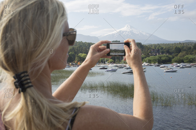 Woman takes smart phone pic over lake, Villarica volcano