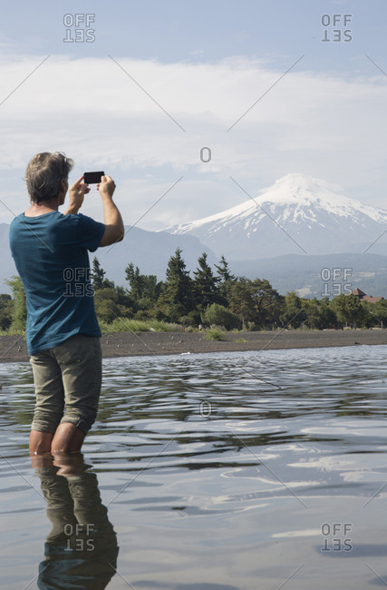Man takes smart phone pic across lake, Villarica volcano