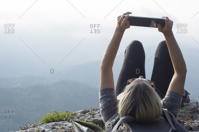Mature woman hiker reclines on cliff edge with pad