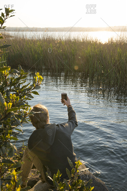 Young man takes selfie on edge of pond