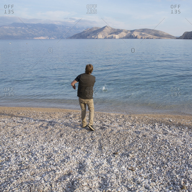 Young man skips rock into sea in barren landscape