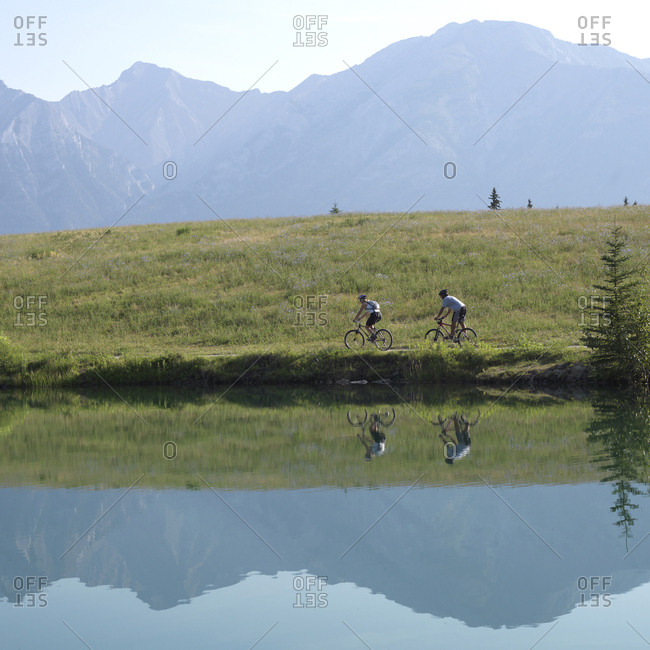 Two mountain bikers on path along mountain lake