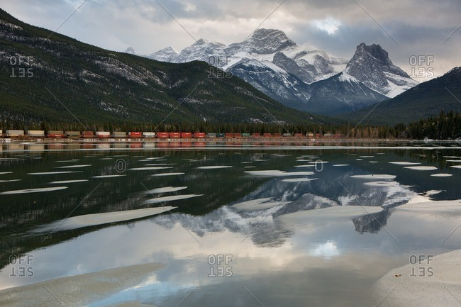 Canada, Alberta - August 3, 2013: Mountains and train relected in lake