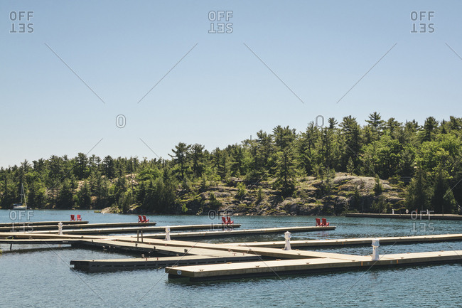 Red Adirondack Chairs Placed At Each End Of A Wharf For The Locals And Tourists In The Municipality Of Killarney, Ontario