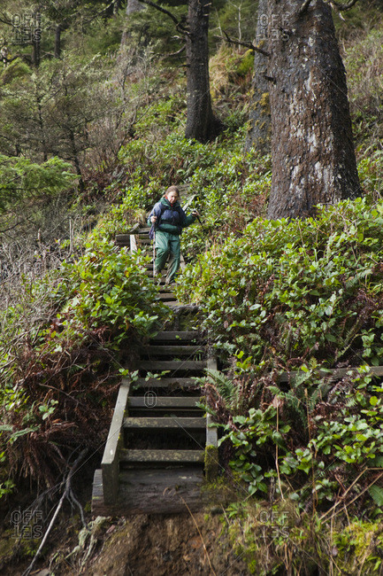 A hiker walks down the wooden steps leading down to Third Beach, Olympic National Park, Washington.