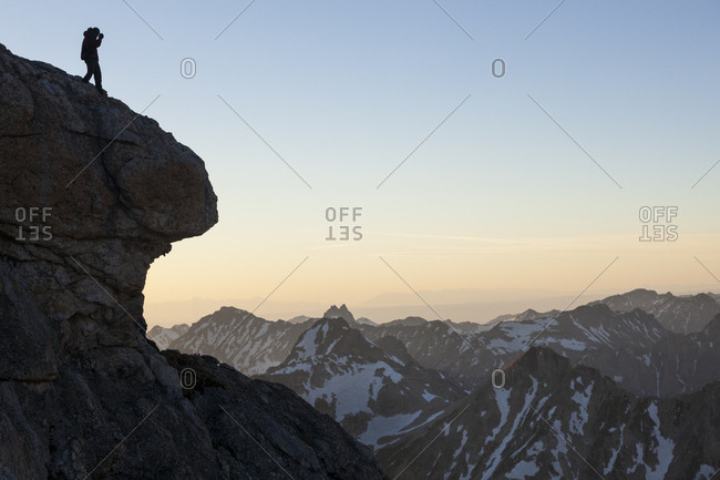 A man stands on a cliff edge taking photos in Grand Teton National Park, Wyoming.