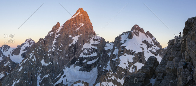 A climber stands on the edge of a cliff with a view of Grand Teton at sunrise in Grand Teton National Park, Wyoming.