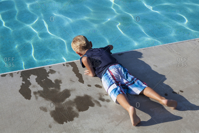 A boy leans over the edge of a swimming pool in Grandview, Washington.