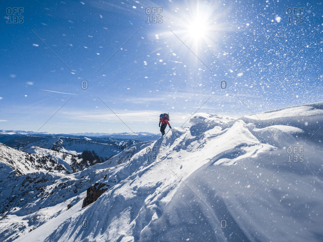 A hiker steps over a small cornice as snow swirls around them in White River National Forest, Colorado.
