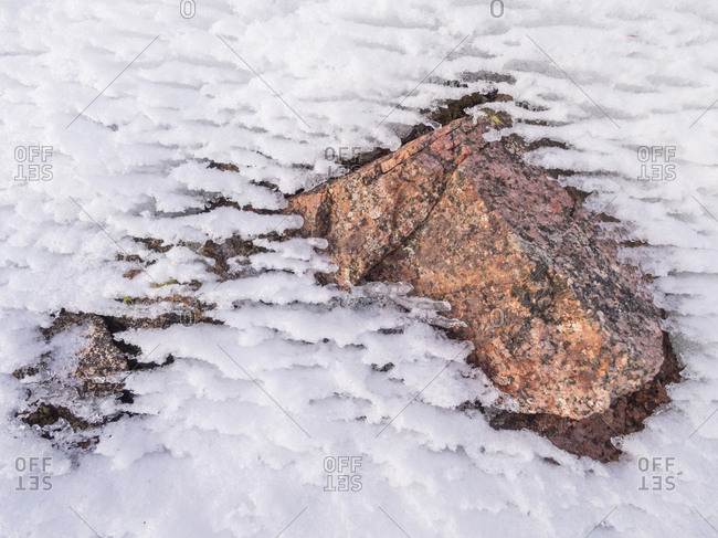 Pink granite protrudes through the snow in White River National Forest, Colorado.