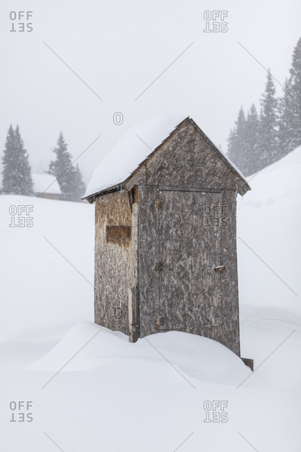 An outhouse buried in snow at a backcountry cabin above Red Mountain Pass, San Juan National Forest, Colorado.
