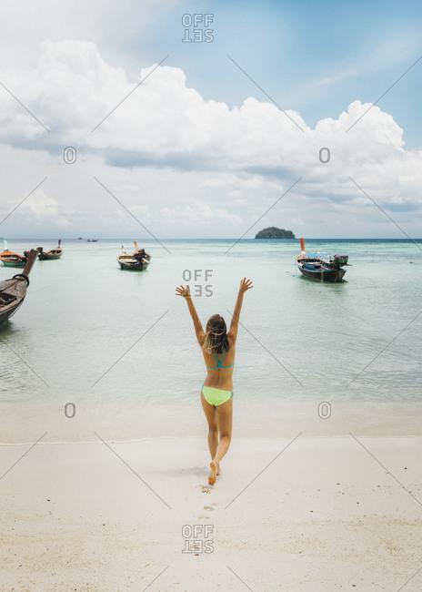 Young woman in bikini walking on beach towards sea with raised arms, Tambon Ko Tarutao, Chang Wat Satun, Thailand