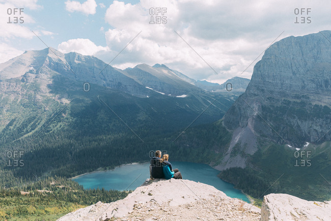 Couple sitting on cliff, Glacier National Park, Montana, USA
