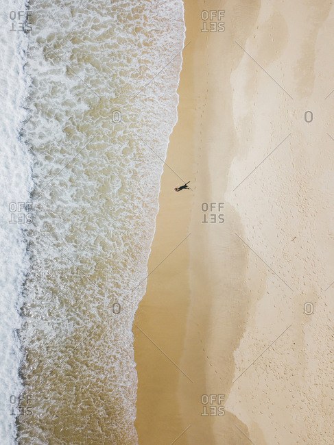 A girl on enormous Australian beach from above