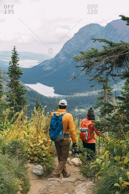 Couple's hiking beautiful trail in Glacier National Park, Montana