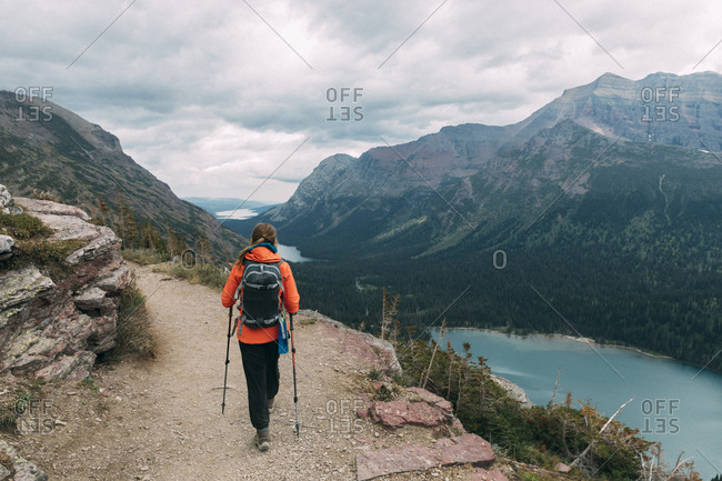 A girl is hiking beautiful mountain trail in Glacier National Park, Montana