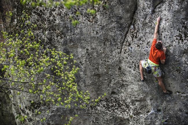 Man rock climbing up cliff, Jura, Olkusz, Malopolskie Province, Poland