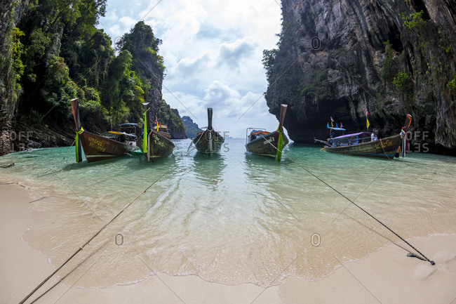 Thailand, Krabi, Tonsai Beach - December 25, 2014: Six wooden long tail boats anchored to a small sandy beach on a island in Krabi, Thailand.