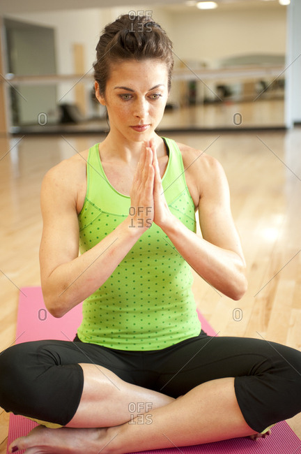 A young woman in a salutation yoga pose.