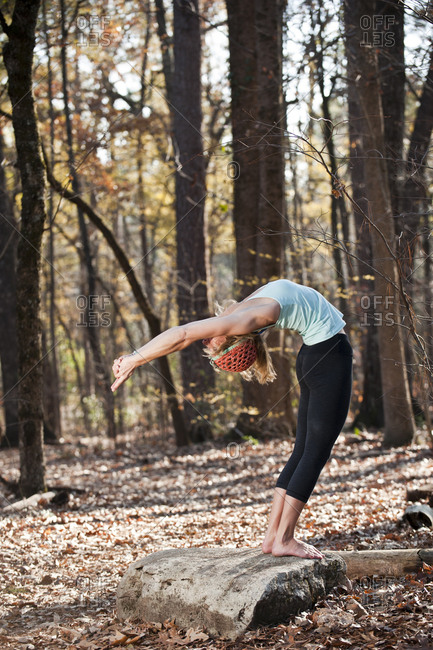 A woman doing yoga postures in outdoor setting.