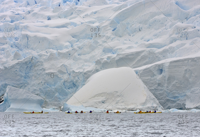 A group of kayakers paddle close to the edge of a glacier in Graham Passage, Antarctica.