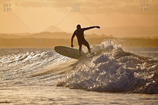 A surfer catches a wave at T-Tree Point, Noosa Heads, Queensland, Australia.