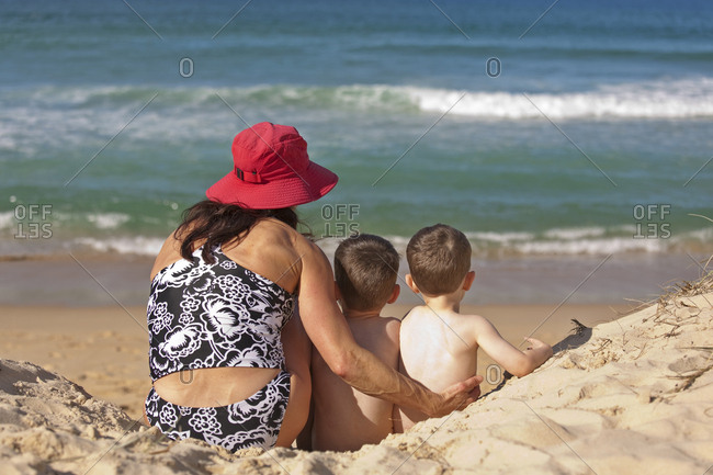 A woman and two children sitting on the sand at Sunshine Beach, Queensland, Australia.