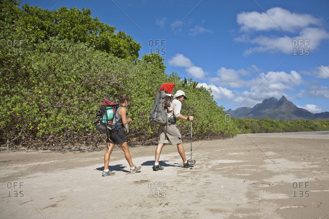 A man and woman with their baby hike along Zoe Bay, Hinchinbrook Island, Queensland, Australia.