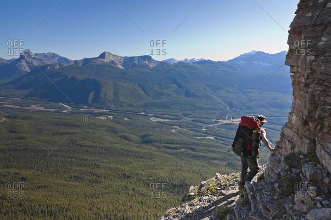 A hiker traverses a ledge, Castle Mountain, Banff National Park, Alberta, Canada.